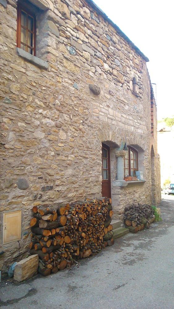 maison pierre et bûches de bois