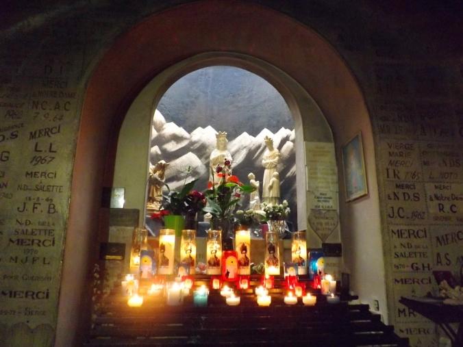bougies et ex voto devant la stautue de notre dame de la salette