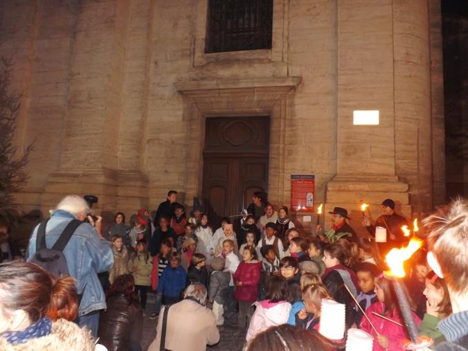Les enfants de la calandreta chantent devant la collégiale lors de la pegoulade pezenass decembre 2015