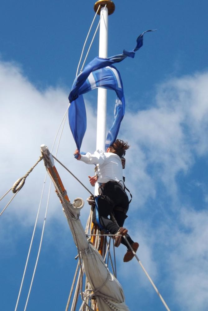 matelot qui attache le drapeau au sommet du mat du Shtandart russe